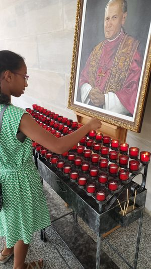 Black Girl Lighting A Candle at Pope Saint John Paul II Shrine - Catholic Stock Photo